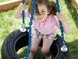 girl playing on tire swing
